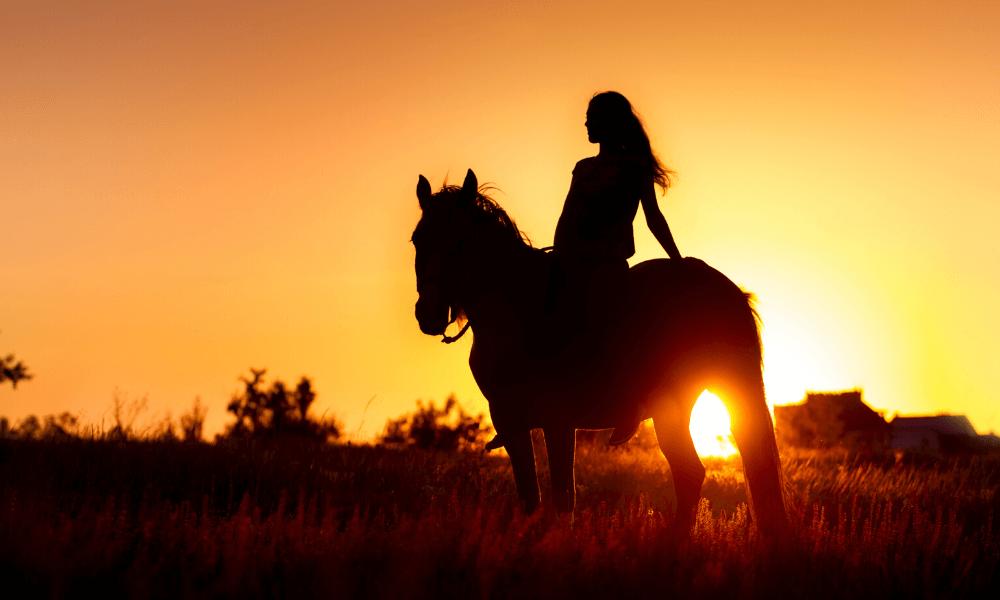 woman on horseback at sunset