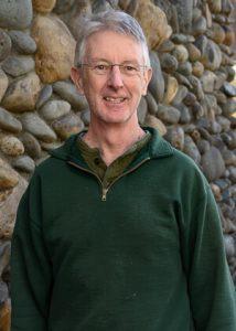 Chris Moffitt in front of stone rockwall